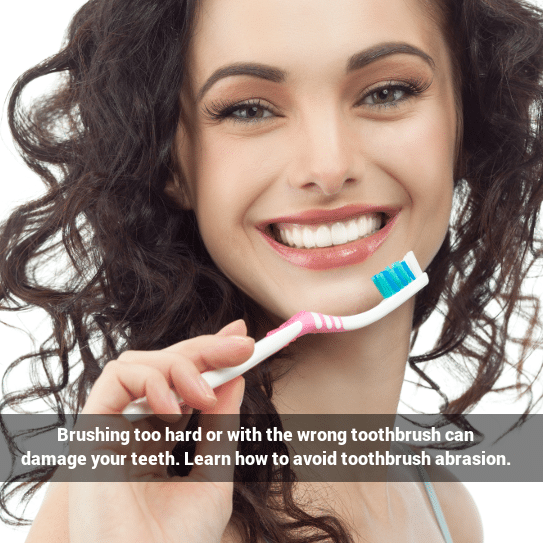 Preventing toothbrush abrasion: A woman with a smile holding up a toothbrush