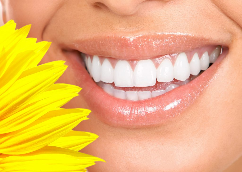close up of woman's smile with a yellow flower