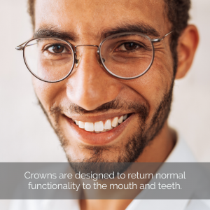 Dental crowns: A man with glasses smiles with healthy looking teeth.