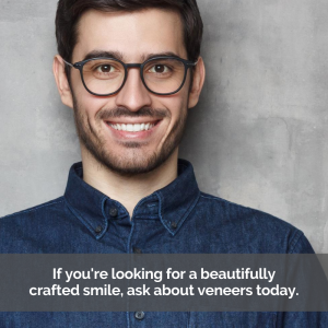 Man smiling about veneers in front of gray backdrop.