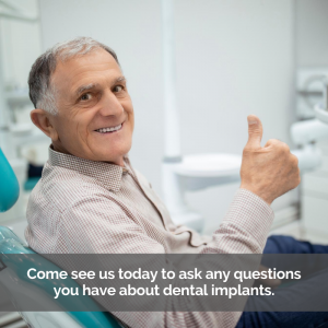 An elderly man gets dental implants. He sits in a dental chair giving the thumbs up with a smile.