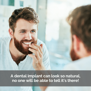 A man looking at his dental implants in the mirror.