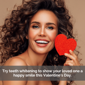 Beautiful woman with white teeth smiling while holding up a paper heart.