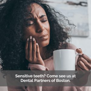 Sensitive teeth cause a woman to hold her cheek in pain while drinking coffee.
